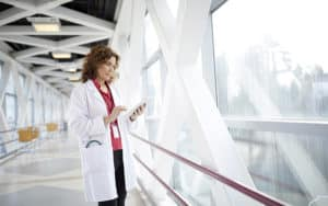 Doctor Using Digital Tablet While Standing In Hospital Corridor